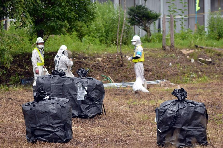 A 2015 file photo shows workers cleaning the area during a decontamination operation in the village of Iitate in Fukushima prefecture.