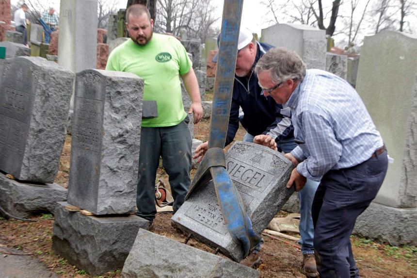 Toppled Jewish headstones are set back in place after a vandalism attack on a Jewish cemetery in St Louis, Missouri.