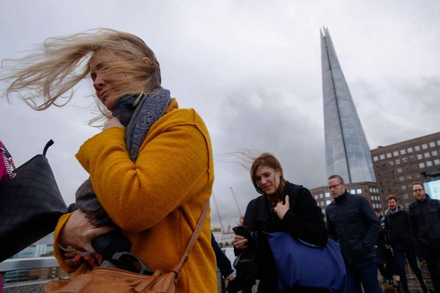 High winds blows commuters hair as they cross London Bridge, in view of The Shard, during the approach of the 'Storm Doris' weather front in London, UK.