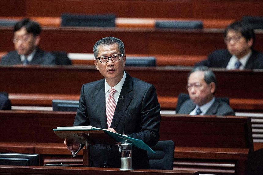 """Mr Chan delivering the 2017 Hong Kong budget speech at the Legislative Council yesterday. With a surplus of HK$92.8 billion (S$17 billion), the former development minister announced billions in tax cuts and poverty relief in a budget hailed as """"forwa"""