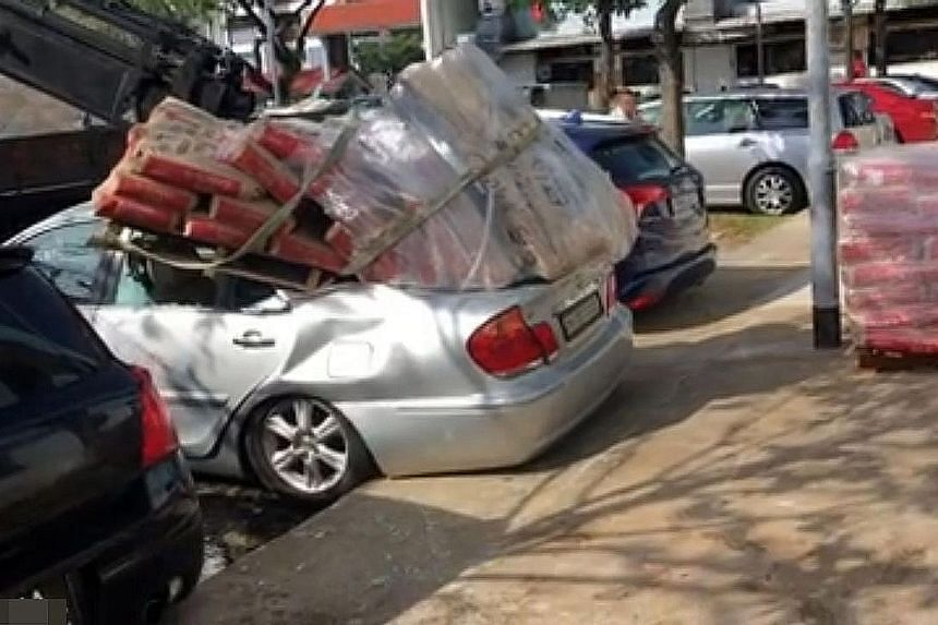 The silver Toyota was at a carpark near Block 727, Clementi West Street 2 when a lorry crane apparently dropped a pallet filled with cement bags on it. There appeared to be no one in the car at the time.