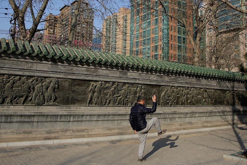 Modern apartment blocks loom as a man goes through the traditional moves of taiji in Beijing. The Chinese authorities have expanded curbs on home purchases and tightened restrictions on property lending in an attempt to avoid a housing bubble and red