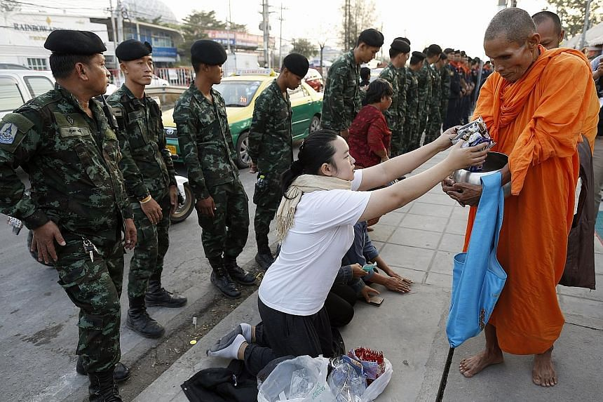 Monks from the controversial temple collecting morning alms outside the compound as soldiers stand guard.