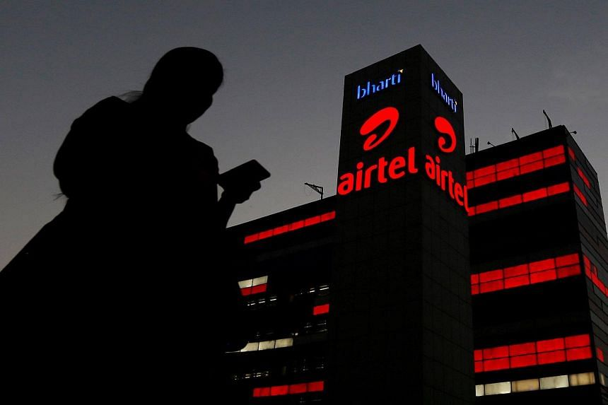 A girl checks her mobile phone as she walks past the Bharti Airtel office building in Gurugram, previously known as Gurgaon, on the outskirts of New Delhi, India.