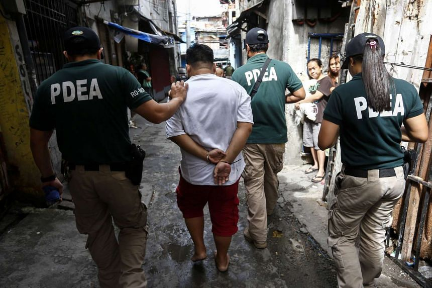 Operatives of the Philippine Drug Enforcement Agency handcuff a man suspected of involvement in illegal drugs during a raid in a residential district of Pasig City, Philippines on Feb 13, 2017.