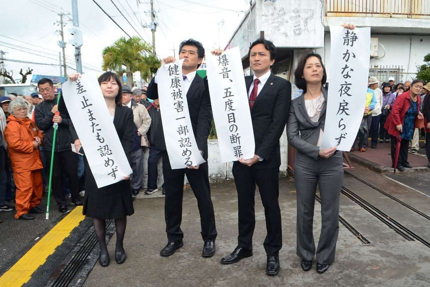 Lawyers of the plaintiffs' side react after receiving a judgment that dismissed the request for the suspension of US military flights in Okinawa on Feb 23, 2017.