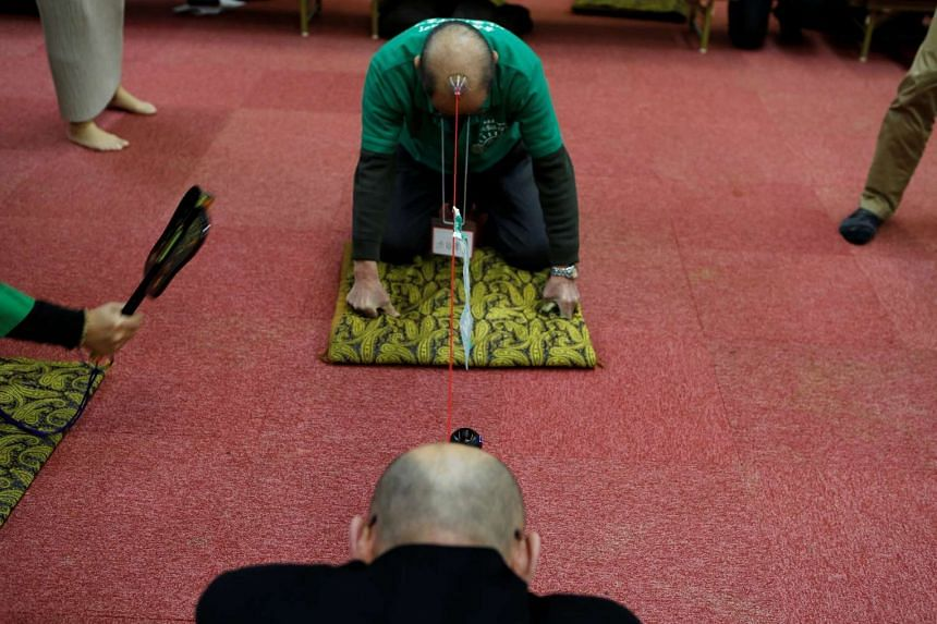 Members of the Bald Men Club, take part in a unique game of tug-of-war by attaching suction pads onto their heads, at a hot spring facility in Tsuruta town, Aomori prefecture, Japan, on Feb 22, 2017.