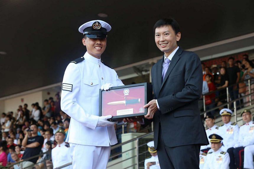 Minister of State for Communications and Information, and Health, Mr Chee Hong Tat, (right) presenting the Golden Bayonet to Specialist Cadet (SCT) Yeo Jun Yu Zachary.