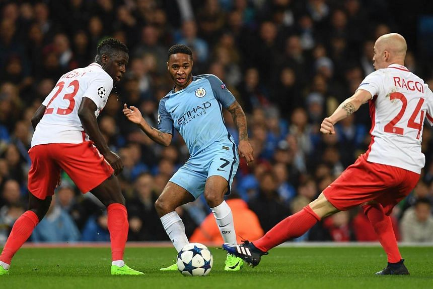 Manchester City's English midfielder Raheem Sterling (centre) trying to thread the ball between Monaco's French defender Benjamin Mendy (left) and Monaco's Italian defender Andrea Raggi during the UEFA Champions League Round of 16 first-leg football