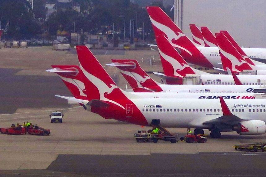 Groundstaff working on the tarmac next to Qantas Airways planes parked at Sydney's Domestic Airport terminal in Australia.