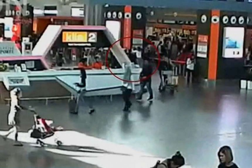 A man purported to be Kim Jong Nam being accosted by a woman in a white shirt at Kuala Lumpur International Airport on Feb 13, 2017.