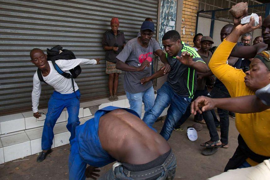 A vigilante mob attacks a Nigerian migrant outside a church in Pretoria, Feb 18, 2017.