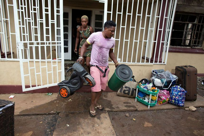 A Nigerian man gathers his belongings after his house was burned out by a vigilante mob in Pretoria, Feb 18, 2017.
