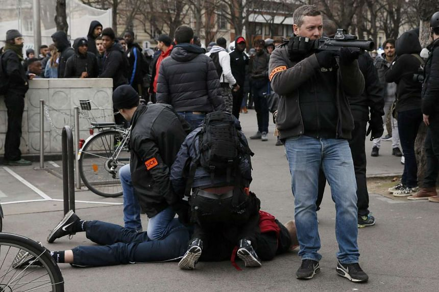 French plain-clothes police apprehend a youth during a protest in Paris, Feb 23, 2017.