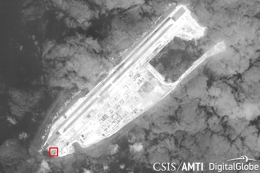 A satellite image appears to show concrete structures with retractable roofs on the artificial island Fiery Cross Reef.