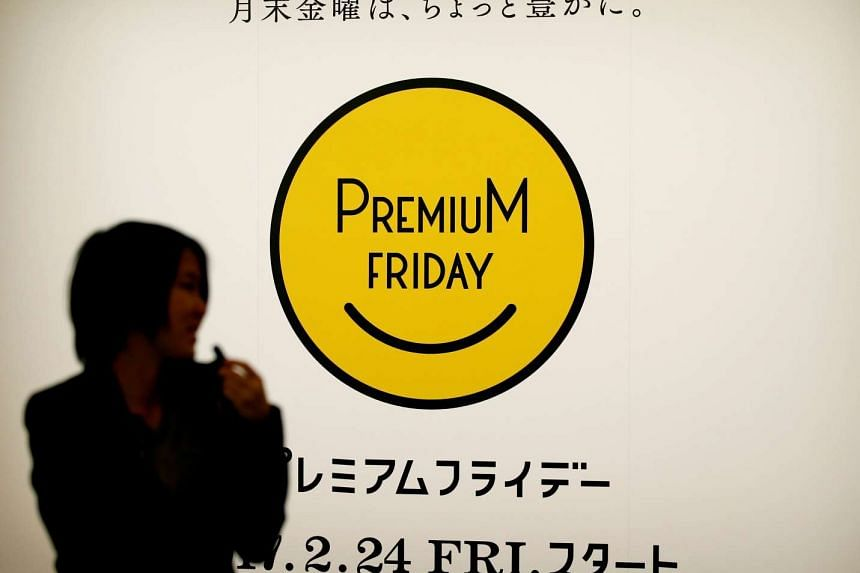 A woman walks past the logo of Premium Friday campaign in Tokyo, Japan, on Feb 21, 2017.