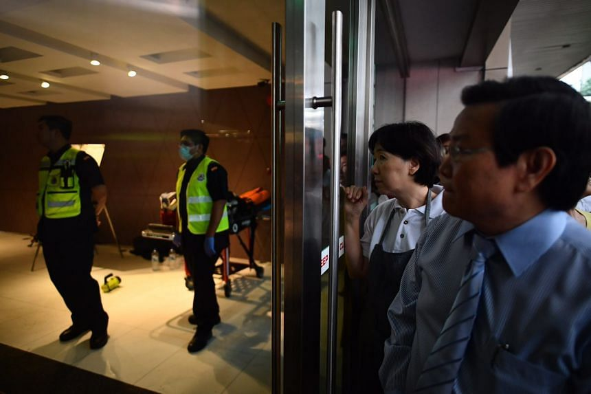 People look on from outside as SCDF officers respond to a fire at Shenton House on Feb 24, 2017.
