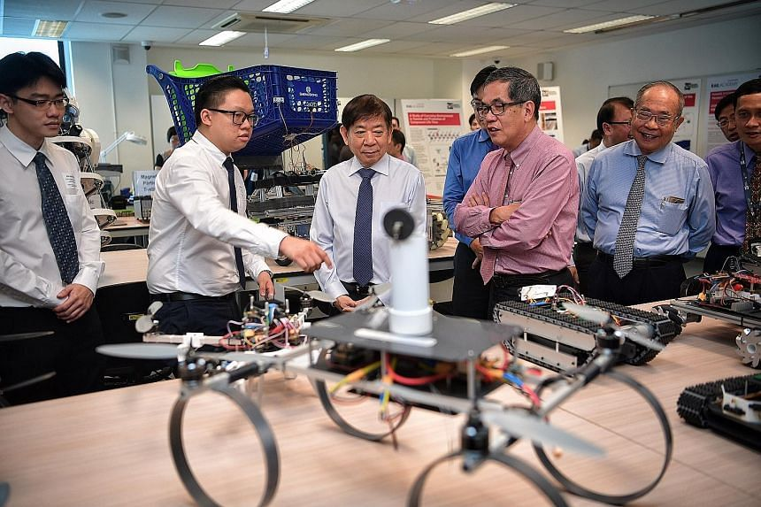 Mr Samuel Tan (second from left), 24, a second-year SIT student taking a Bachelor of Engineering with Honours in Systems Engineering course, showing Transport Minister Khaw Boon Wan (in blue tie) a series of student prototypes at the Systems Engineer