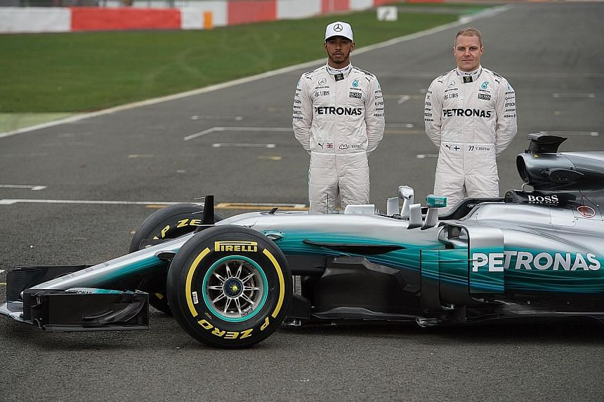 """Mercedes drivers Lewis Hamilton (left) and Valtteri Bottas posing by the Mercedes W08, the team's new car for the season starting on March 26. Testing will start in Barcelona on Monday and team boss Toto Wolff has said that Mercedes are """"buzzing with"""