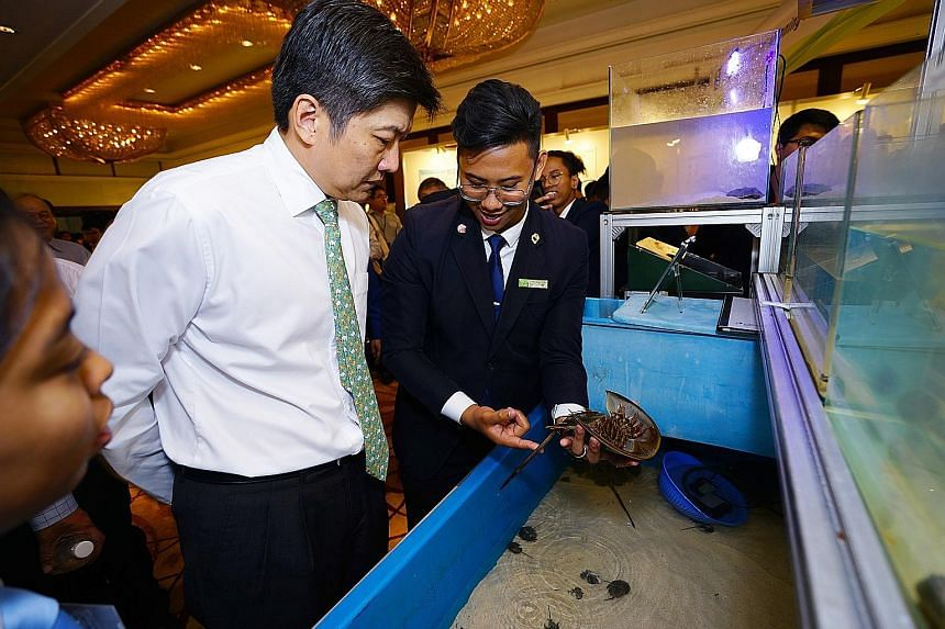 Mr Eunos Chong yesterday showing Education Minister (Schools) Ng Chee Meng a horseshoe crab his team had bred in captivity using a system it developed. The team topped the junior college/ITE category.