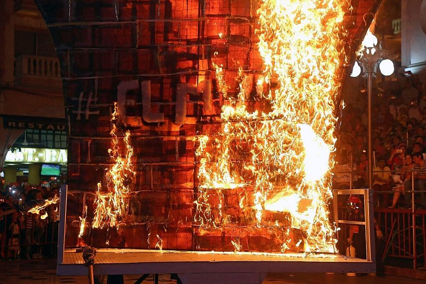 A fake wall being burned in a protest against Mr Donald Trump in the Mexican city of Veracruz. The US President may reallocate US aid to funds for a border wall.
