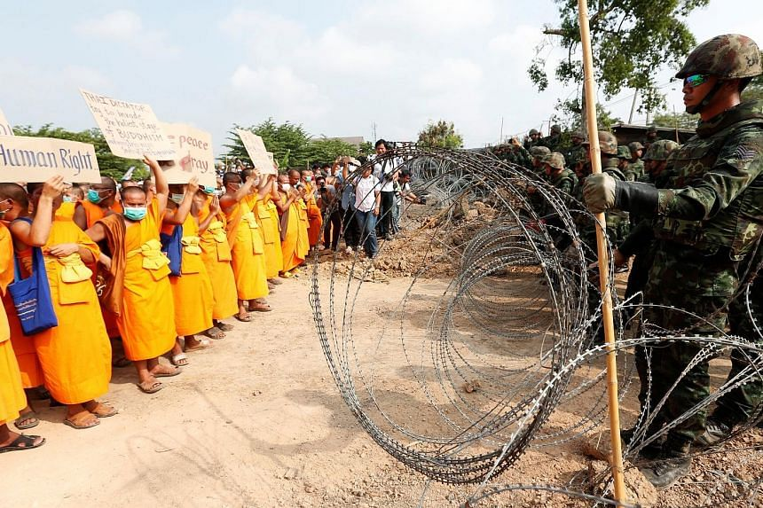 Defiant Buddhist monks stood up to a row of soldiers, with a wire barricade separating the two groups, in Pathum Thani province yesterday. Talks yesterday between officials and the Dhammakaya temple's senior monks broke down, raising the possibility