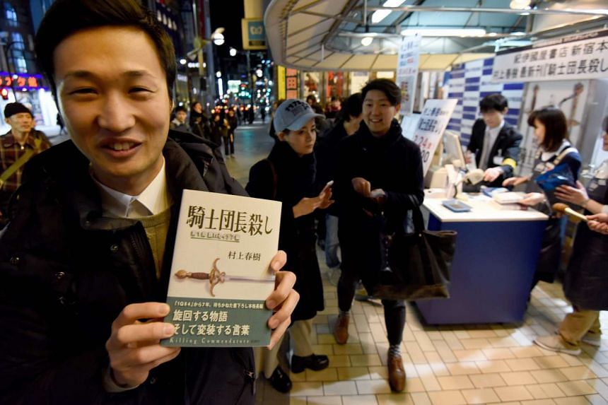 A fan of Haruki Murakami holding his new novel at a bookstore in Tokyo, in the early hours of Feb 24, 2017.