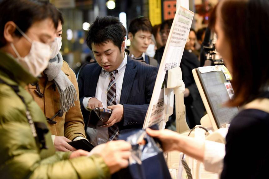 A fan of Haruki Murakami preparing to pay at a bookstore in Tokyo, in the early hours of Feb 24, 2017.