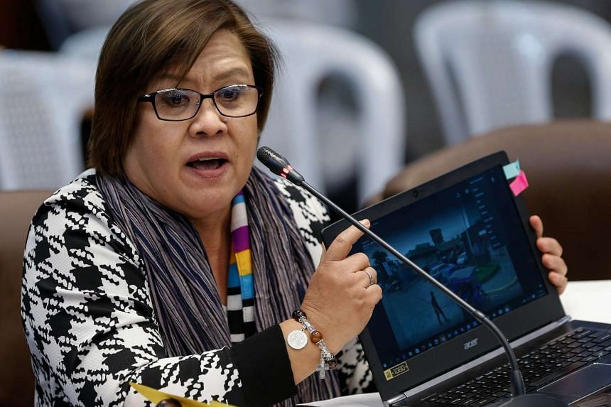Senator Leila De Lima showing pictures of a crime scene on a laptop during a hearing on extrajudicial killings and summary executions of suspected criminals at the Philippine Senate in Pasay City, south of Manila, on Sept 15, 2016.