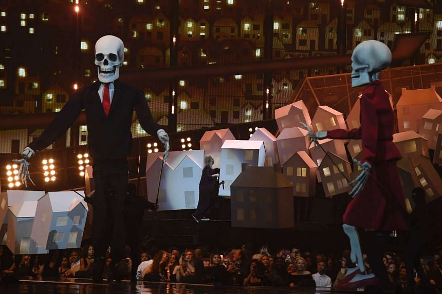 Katy Perry (centre) performing amid dancing houses and two giant skeletons.
