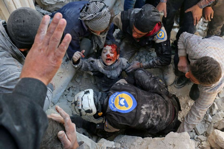 White Helmet rescuers free a boy from the rubble following a reported barrel bomb attack in Aleppo, Nov 24, 2016.