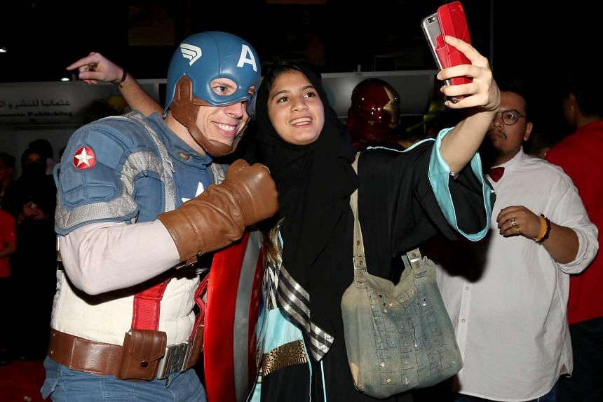 A woman taking a selfie with a man dressed as Captain America during the Jeddah Comic-Con in Saudi Arabia on Feb 16, 2017.