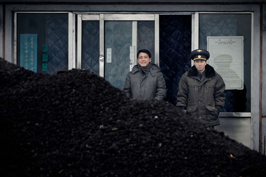 File photo of a North Korean military officer (right) and a North Korea man standing behind a pile of coal along the banks of the Yalu River in the northeast of the North Korean border town of Siniuju, on Dec 14, 2012.