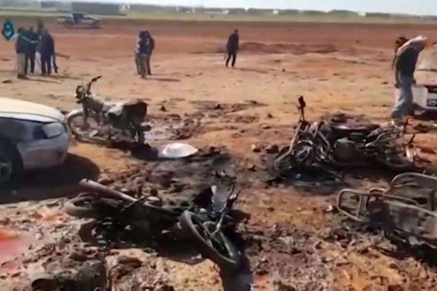 A still image from social media shows people inspecting the damage at a site of an ISIS car bomb blast.