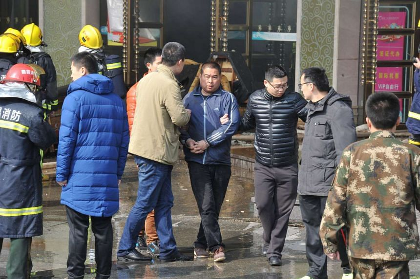 A man being taken away by police from HNA Hotel after a fire broke out in Nanchang, Jiangxi province, on Feb 25, 2017.