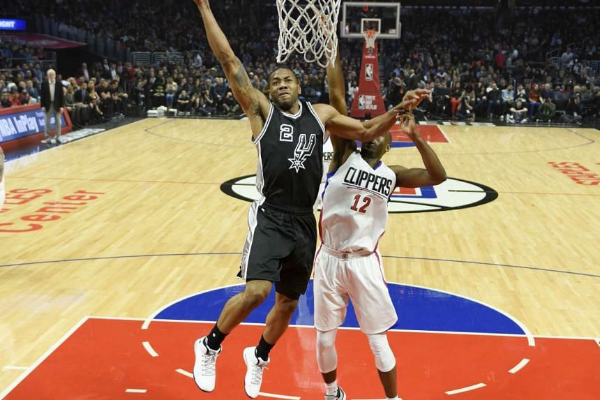 San Antonio Spurs forward Kawhi Leonard (2) goes up for a dunk in front of LA Clippers forward Luc Mbah a Moute (12) during the first quarter at Staples Center.