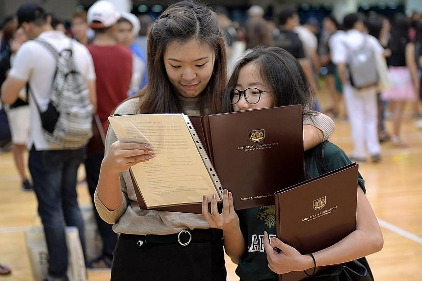 Two former Raffles Institution students looking pleased with their exam results at the school. The last three cohorts for the A levels got the three highest pass rates since the curriculum was last revised.