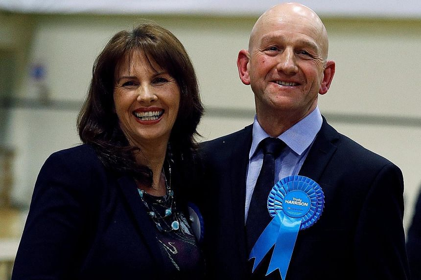 Above: Conservative candidate Trudy Harrison with her husband, Keith, after her victory in the Copeland by-election on Thursday. Right: Labour's Mr Gareth Snell (in dark suit) celebrating with his wife, Sophia, and party members after winning the Sto