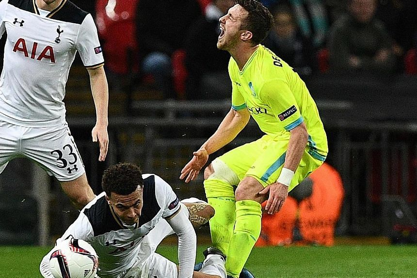 Dele Alli was red-carded after his studs-up challenge on Gent's Brecht Dejaegere (right) that saw him sent off in the 40th minute. Spurs fought valiantly but were held to a 2-2 draw by Gent and exited the Europa League, having been beaten 3-2 on aggr