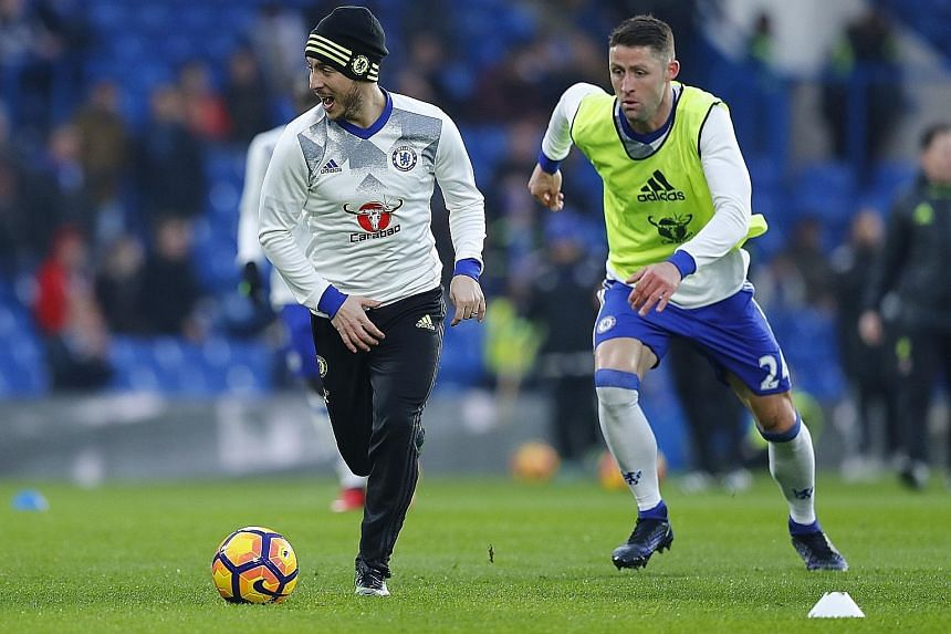 Eden Hazard (left) and Gary Cahill warming up before Chelsea's 2-0 win over Hull last month. The league leaders are looking hard to shake off.
