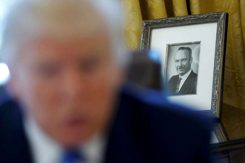 "A photograph of Mr Trump's late father, Mr Fred Trump, behind him in the White House on Thursday. In his interview with Reuters, he said China could solve the national security challenge posed by North Korea ""very easily if they want to"", and a"