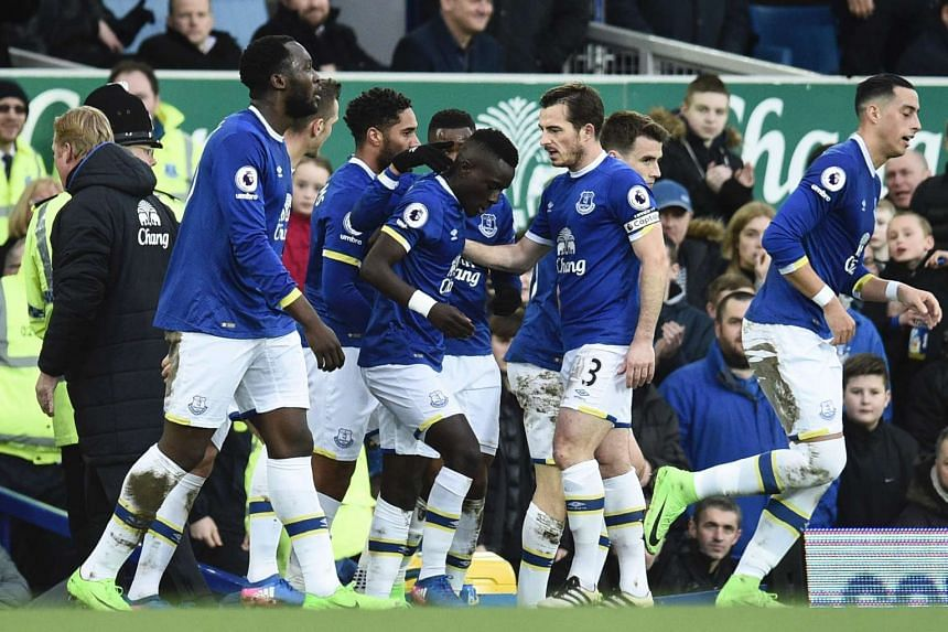 Everton players congratulate Everton's Senegalese midfielder Idrissa Gueye (centre) after he scored the opening goal.