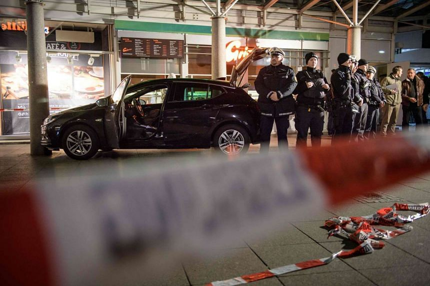 Police officers stand around a car in front of a business building in Heidelberg, western Germany, where a man ploughed into pedestrians before beeing shot by the police on Feb 25, 2017.