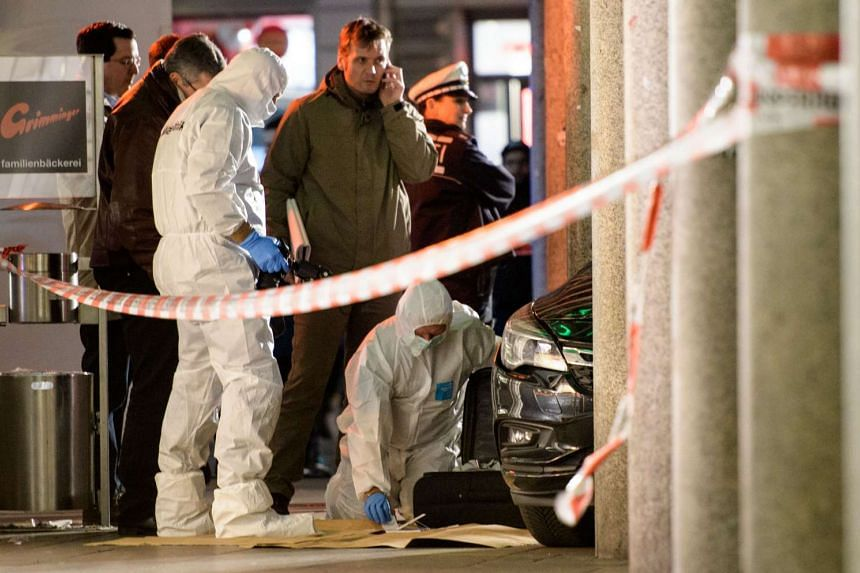 Police officers investigate a car in front of a business building in Heidelberg, western Germany, where a man ploughed into pedestrians before beeing shot by the police on Feb 25, 2017.