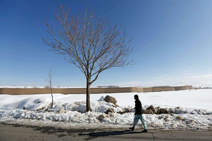 A man walks along a street covered with snow on the outskirts of Kabul, Afghanistan.