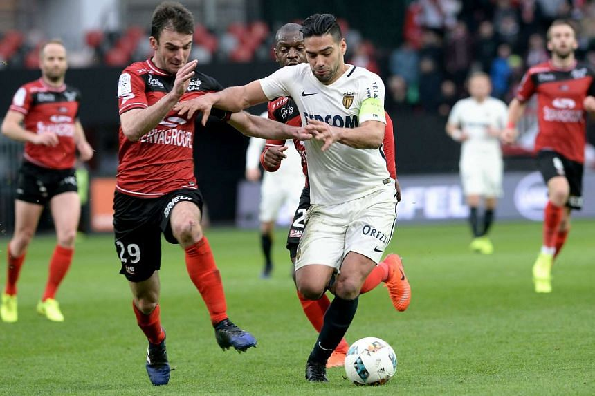 Monaco's Colombian forward Radamel Falcao (right) outruns Guingamp's French midfielder Christophe Kerbrat during their French L1 football match on Feb 25, 2017 at the Roudourou stadium.
