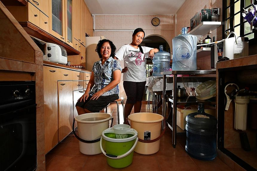 Madam Yeong, 62, and her helper Fatimah, 35, save water from the washing machine's rinse cycles to wash the floors and flush toilets.