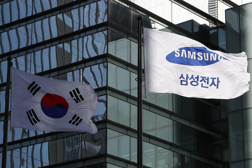 The South Korean national flag(left) and Samsung Electronics Co.'s corporate flag fly outside the company's Seocho office building in Seoul, South Korea.