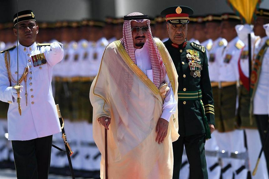 King Salman Abdulaziz Al-Saud inspects a ceremonial guard of honour during a welcoming ceremony at the Parliament House in Kuala Lumpur on Feb 26, 2017.