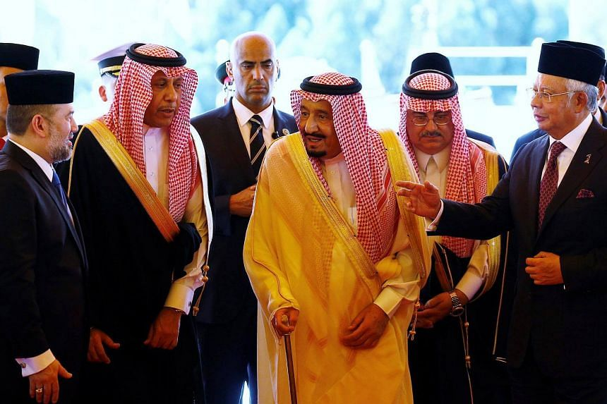 King Salman Abdulaziz Al-Saud leaves after inspecting the honour guard with Malaysia's Prime Minister Najib Razak (right) and Malaysia's King Muhammad V.